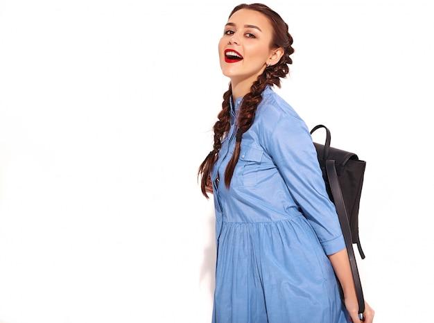 Retrato de joven modelo de mujer sonriente feliz con maquillaje brillante y labios rojos con dos coletas en manos en verano colorido vestido azul y mochila aislado