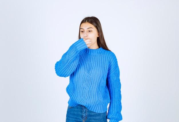 Retrato de una joven modelo en suéter azul silbando con los dedos.