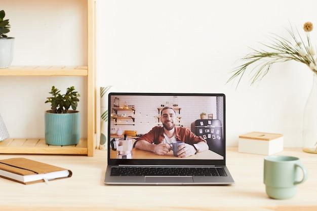 Retrato de joven en el monitor de la computadora sonriendo tiene conversación en línea