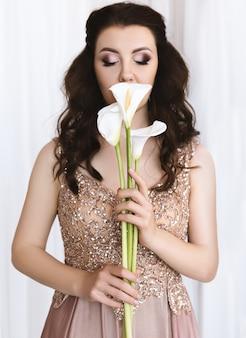 Retrato de joven morena bella mujer europea en vestido de oro con flores frescas de cala blanca sobre fondo blanco.