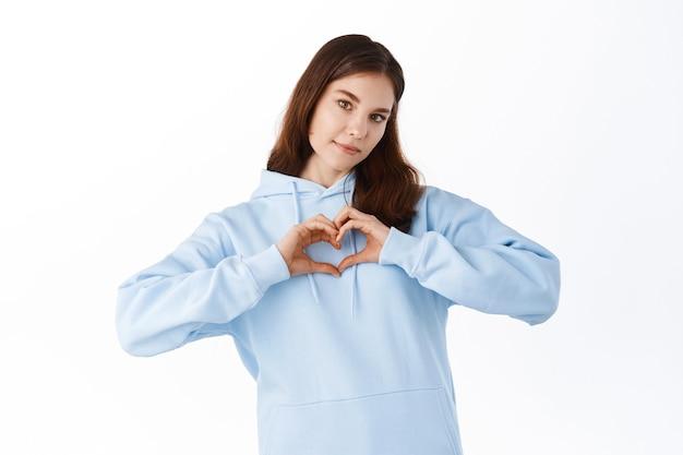 Retrato de joven, morena, chica guapa en sudadera con capucha mostrando con su dedo la figura del corazón, enviando amor a su amante, de pie sobre una pared blanca