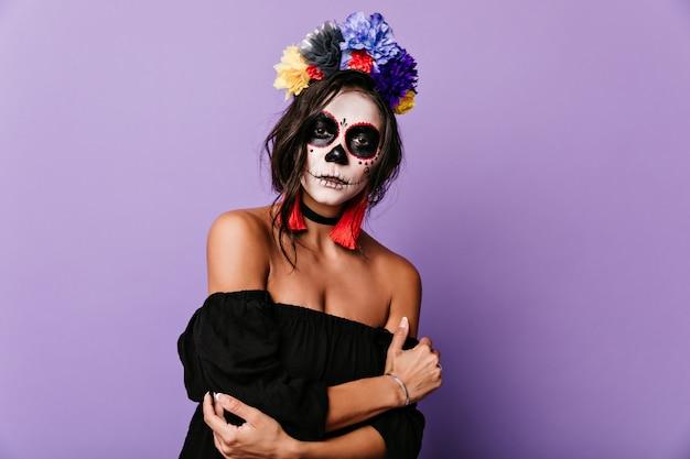Retrato de joven morena con corona de flores multicolor. mujer con máscara de esqueleto mira misteriosamente
