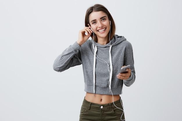 Retrato de joven morena guapa estudiante caucásica en casual gris con capucha y jeans sonriendo con dientes, sosteniendo auriculares y teléfono inteligente con las manos, escuchando su música favorita