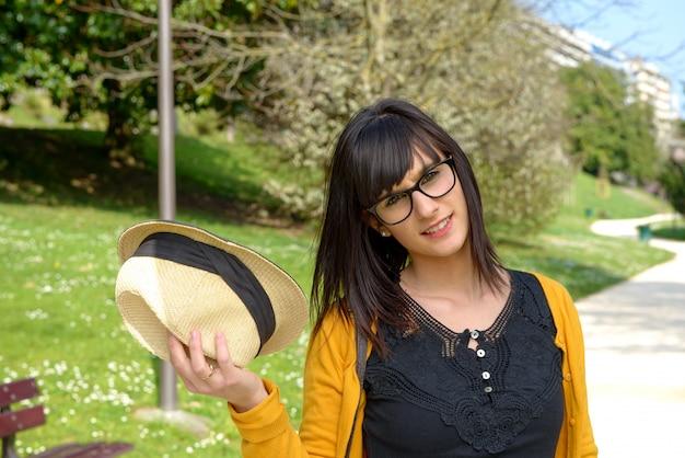 Retrato de joven morena con sombrero de verano en el parque