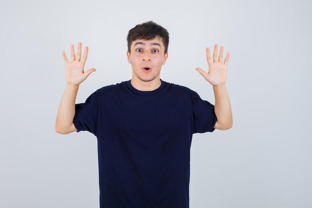 Retrato de joven mostrando gesto de rendición en camiseta negra y mirando asustado vista frontal
