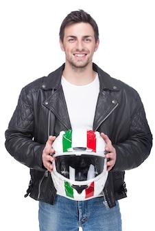 Retrato de un joven motociclista sostiene un casco.