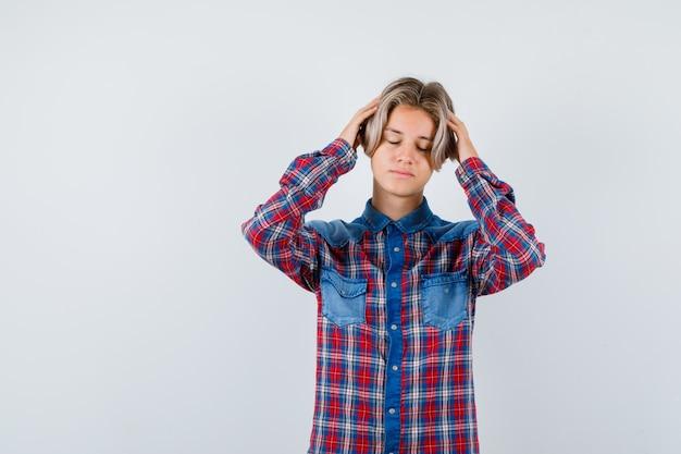 Retrato de joven muchacho adolescente con las manos en la cabeza en camisa a cuadros y mirando agotado vista frontal