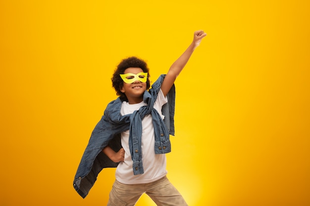 Retrato de un joven muchacho de raza mixta vestido como un superhéroe. bebé negro disfrazado de superhéroe. el ganador y el éxito.