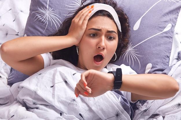 Retrato de joven mujer acostada en la cama sobre una almohada y debajo de una manta con diente de león, estando en casa en su acogedora habitación, mantiene la boca abierta, mirando el reloj con asombrosa expresión facial, llegando tarde.