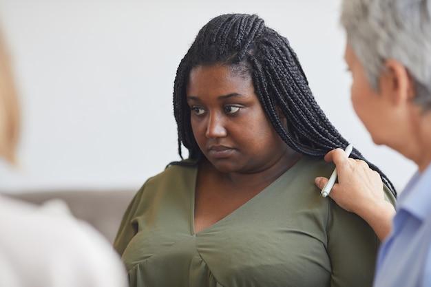 Retrato de joven mujer afroamericana compartiendo historia durante la reunión del grupo de apoyo con psicóloga madura consolándola, espacio de copia