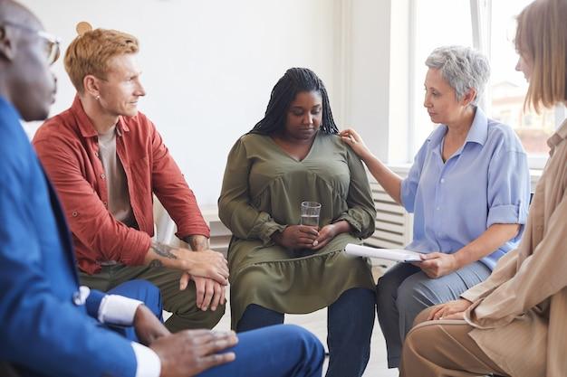 Retrato de joven mujer afroamericana compartiendo luchas durante la reunión del grupo de apoyo con personas sentadas en círculo y consolándola