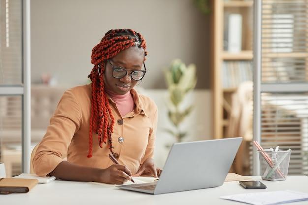 Retrato de joven mujer afroamericana escribiendo en el planificador mientras trabaja o estudia en el escritorio en la oficina en casa, espacio de copia