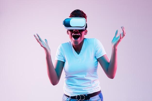 Retrato de joven mujer afroamericana jugando en gafas vr en luz de neón sobre fondo degradado