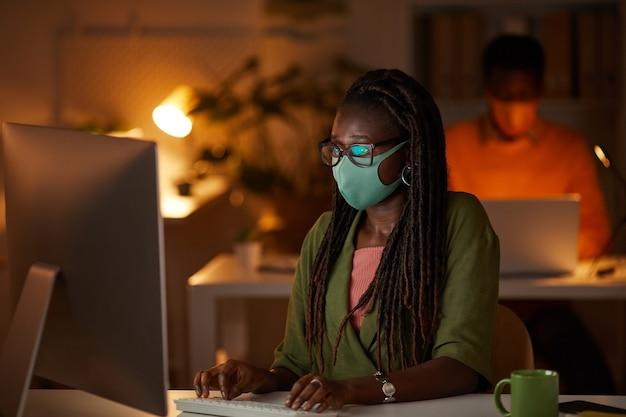 Retrato de joven mujer afroamericana con máscara y gafas mientras trabaja con pc en la oficina por la noche, espacio de copia