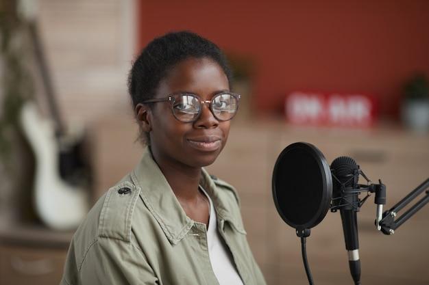 Retrato de joven mujer afroamericana mirando a la cámara mientras está sentado por el micrófono en el estudio de grabación en casa, espacio de copia