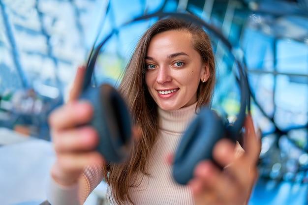 Retrato de joven mujer alegre feliz caucásica atractiva casual moderna sosteniendo auriculares inalámbricos negros
