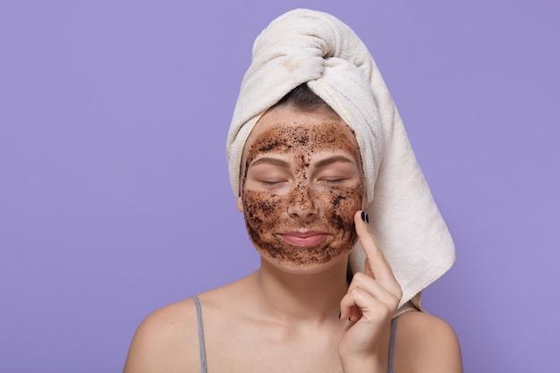 Retrato de joven mujer aplica máscara de arcilla facial casera, tiene una toalla blanca envuelta alrededor de la cabeza, manteniendo los ojos cerrados