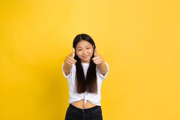 Retrato de joven mujer asiática aislada en la pared amarilla