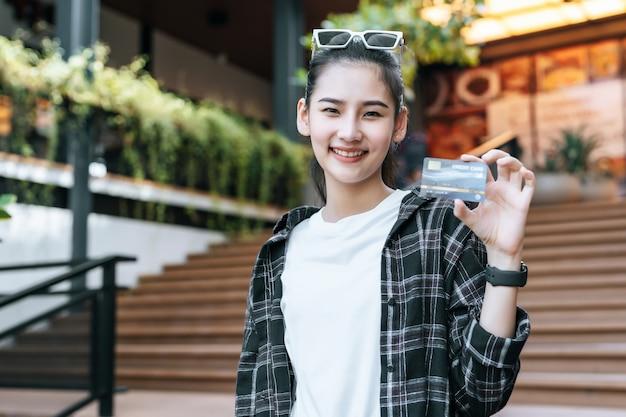 Retrato de joven mujer asiática con anteojos de pie en las escaleras con bolsa de papel de compras