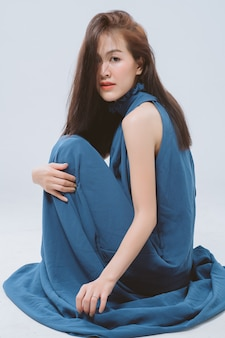 Retrato de joven mujer asiática con cabello largo vestido azul sentado