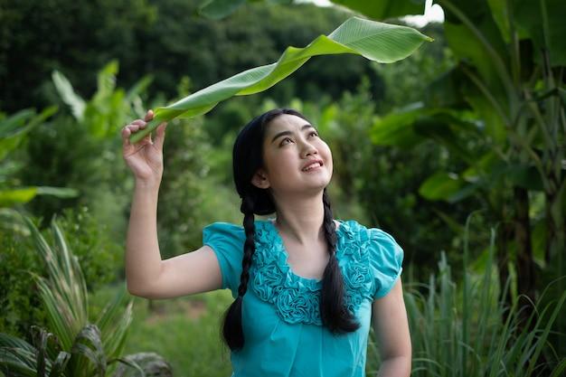 Retrato de una joven mujer asiática con cabello negro sosteniendo una hoja de plátano