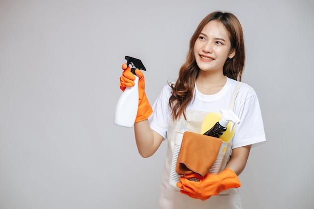 Retrato joven mujer asiática en delantal y guantes de goma, sonrisa y sosteniendo equipo de limpieza en la mano, espacio de copia