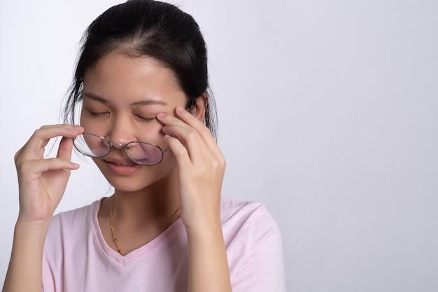 Retrato de joven mujer asiática con gafas con dolor en los ojos en gris