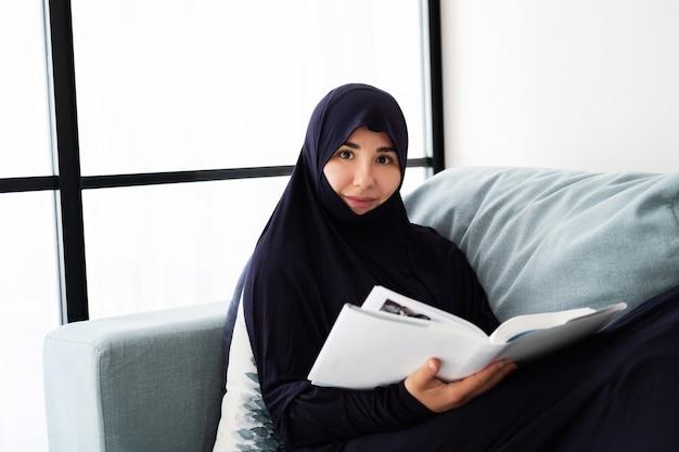 Retrato de joven mujer asiática con hijab, libro de lectura en casa