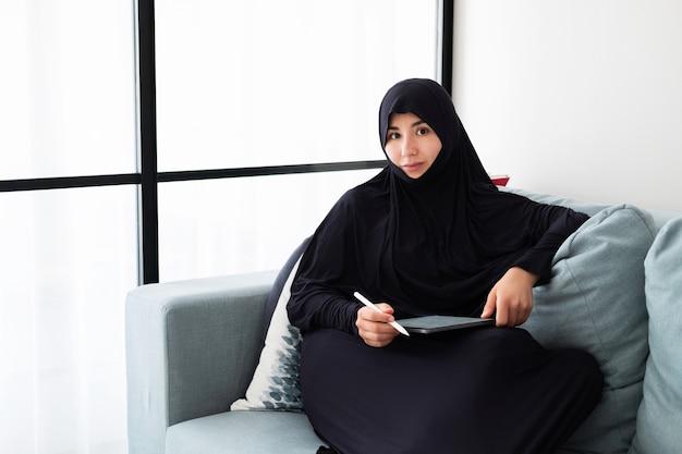Retrato de joven mujer asiática con hijab, trabajando en casa con tableta