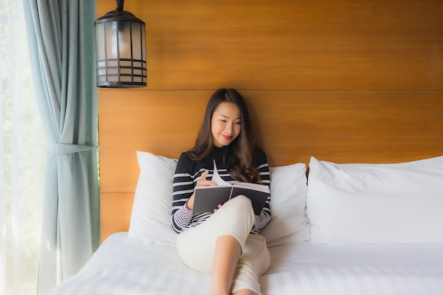 Retrato joven mujer asiática leer libro en dormitorio