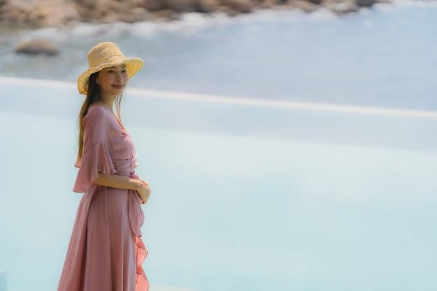 Retrato joven mujer asiática relajarse sonrisa feliz alrededor de la piscina al aire libre en el hotel resort con vista al mar