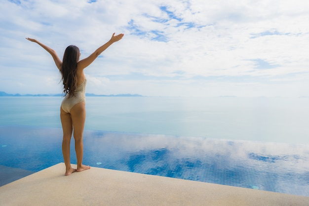 Retrato joven mujer asiática relajarse sonrisa feliz alrededor de la piscina en el hotel y resort