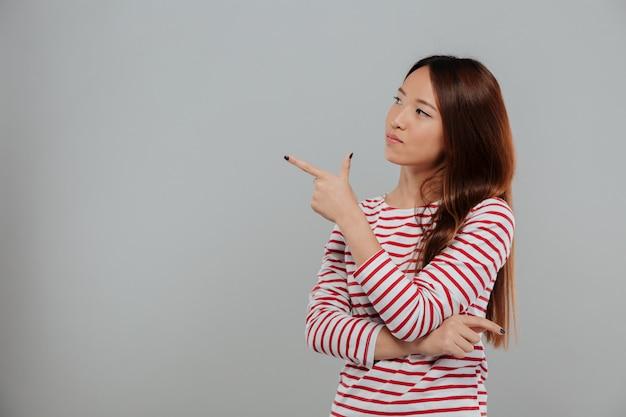 Retrato de una joven mujer asiática señalando con el dedo