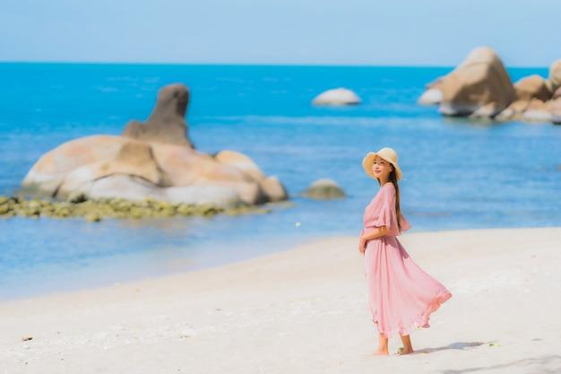 Retrato joven mujer asiática sonrisa feliz alrededor de la playa mar océano con palmera de coco para vacaciones