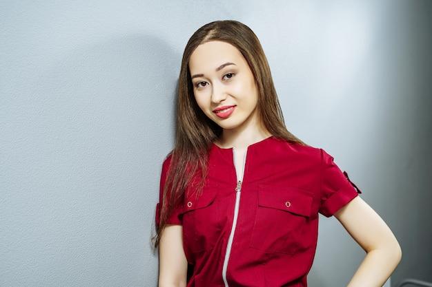 Retrato de joven mujer asiática en uniforme en gris