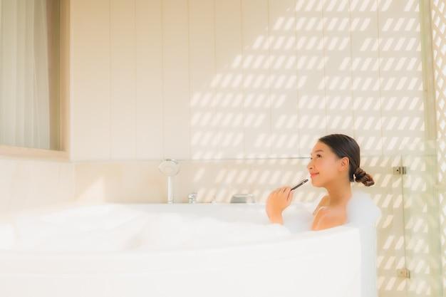 Retrato joven mujer asiática utilizando teléfonos móviles inteligentes en la bañera