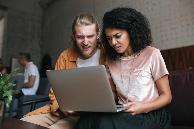 Retrato, de, joven, y, mujer, asombrado, mirar, computadora portátil