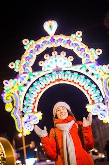 Retrato de joven mujer atractiva divertida sobre fondo nevado de navidad y temporada de vacaciones de invierno