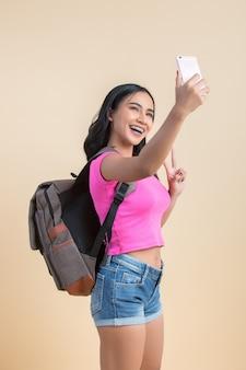 Retrato de una joven mujer atractiva haciendo selfie foto con smartphone