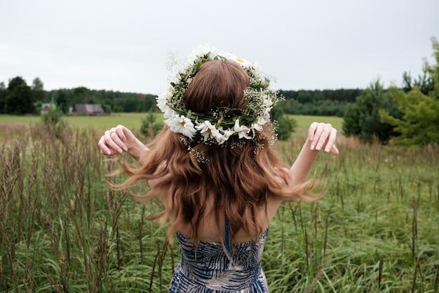 Retrato de joven mujer bonita con diadema de flores de manzanilla en la cabeza.