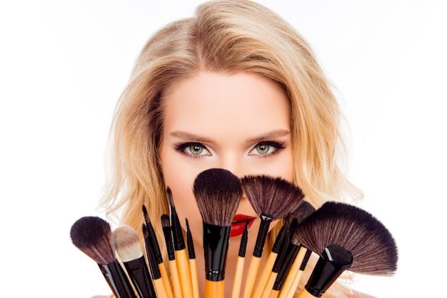 Retrato de joven mujer bonita escondiendo la cara detrás de pinceles de maquillaje