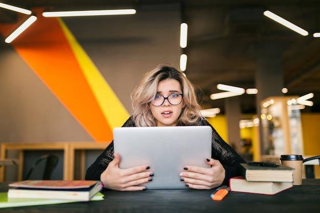 Retrato de joven mujer bonita con expresión de la cara con calcetines, sentado en la mesa trabajando en la computadora portátil en la oficina de co-trabajo, con gafas, estrés en el trabajo, emoción divertida, estudiante en el aula, frustración