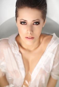 Retrato de joven mujer bonita con el pelo corto disfrutando en el baño en camisa de hombre blanco tocando los labios