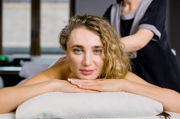 Retrato de joven mujer bonita rubia mirando a cámara disfrutando del procedimiento de masaje manual de espalda. mujer joven que recibe masaje de espalda en el spa