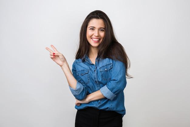 Retrato de joven mujer bonita sonriendo en camisa de mezclilla azul, feliz, estado de ánimo positivo, sonrisa aislada, sincera, cabello largo, mostrando el signo de la paz, estado de ánimo positivo