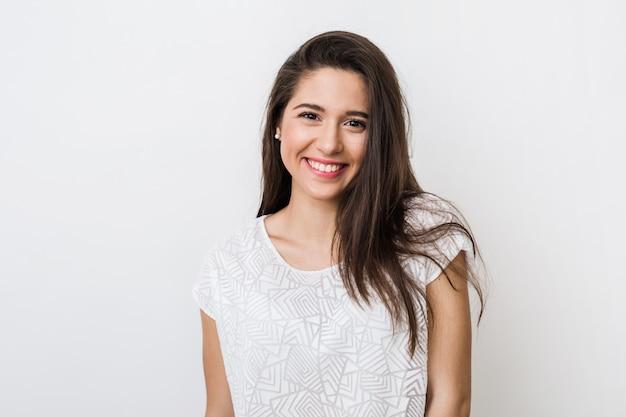 Retrato de joven mujer bonita sonriendo en camiseta blanca, feliz, estado de ánimo positivo, sonrisa aislada, sincera, cabello largo   Foto Gratis