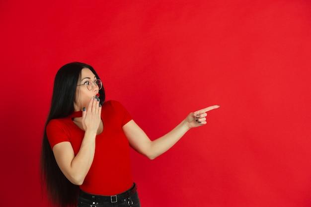 Retrato de joven mujer caucásica con brillantes emociones sobre fondo rojo studio