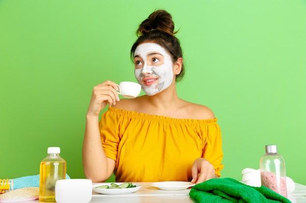 Retrato de joven mujer caucásica en el día de la belleza, rutina de cuidado de la piel y el cabello. modelo femenino tomando café, té mientras se aplica la mascarilla facial. cuidado corporal y facial, belleza natural y concepto de cosmética.