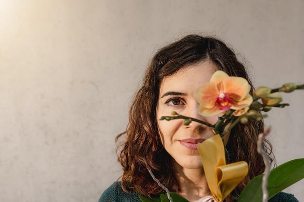 Retrato joven mujer caucásica mirando a la cámara sonríe con una planta de orquídea amarilla delante del ojo.