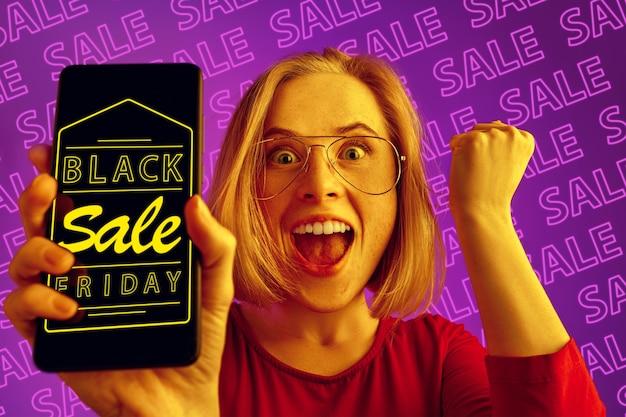 Retrato de joven mujer caucásica mostrando la pantalla del teléfono móvil sobre fondo púrpura